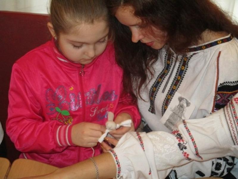 Студентка Лілія Псарук навчає ученицю виготовляти ляльку-мотанку