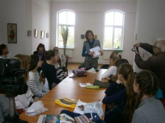 Студентка Ліля Псарук демонструє учням сумку-клатч декорований бойківською вишивкою