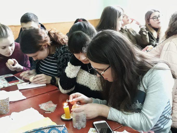 Студенти використовують техніку розпису писачком у створенні великодніх писанок.